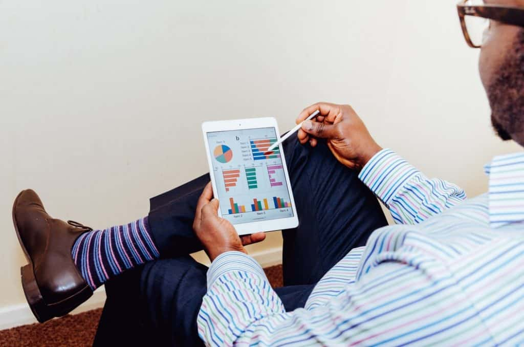 Man is shown wearing colorful socks and doing analytics on a tablet